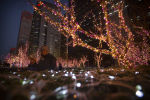 People walk past a display of Christmas lights outside a building in the central business district of Beijing