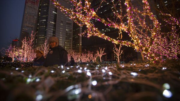People walk past a display of Christmas lights outside a building in the central business district of Beijing - Sputnik Latvija